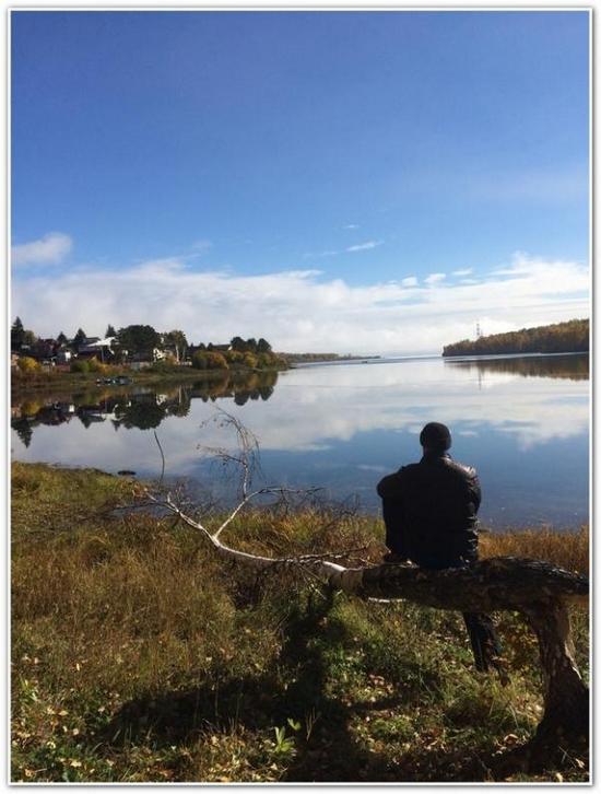 Мужчина на берегу озера сидит на березе