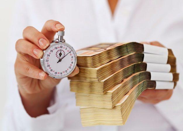 Пачки денег и часы в руках