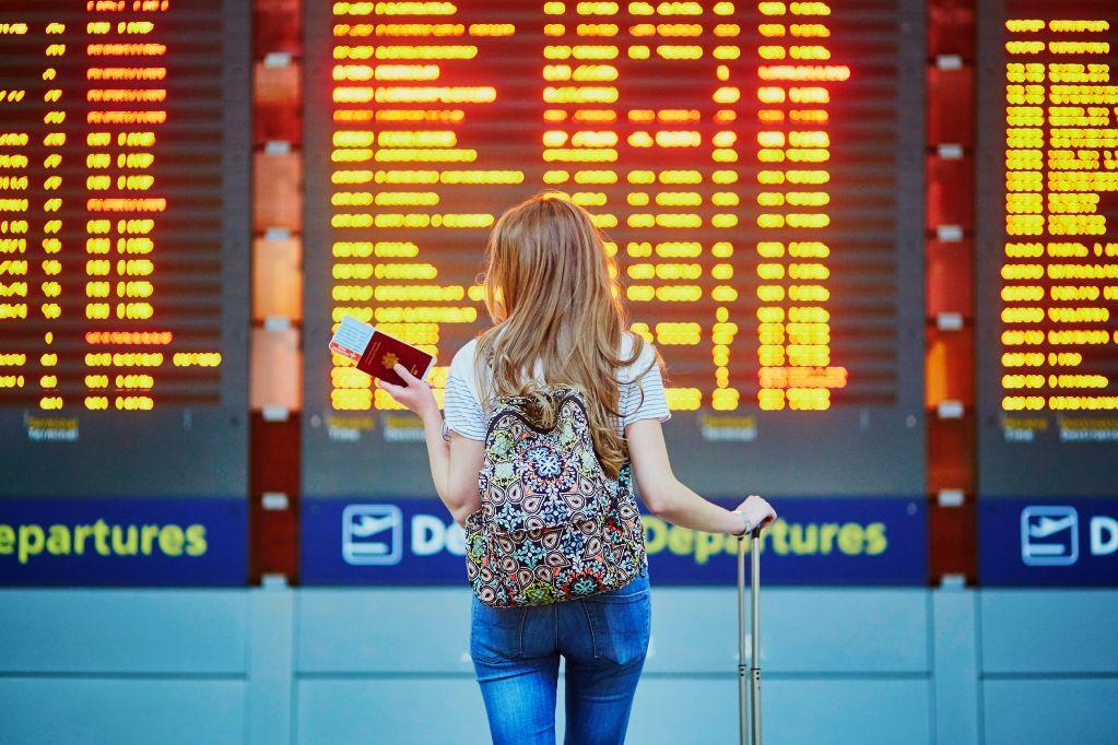 Девушка возле онлайн-табло в аэропорту