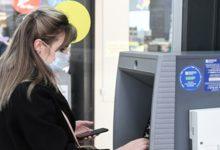Женщина в маске возле банкомата