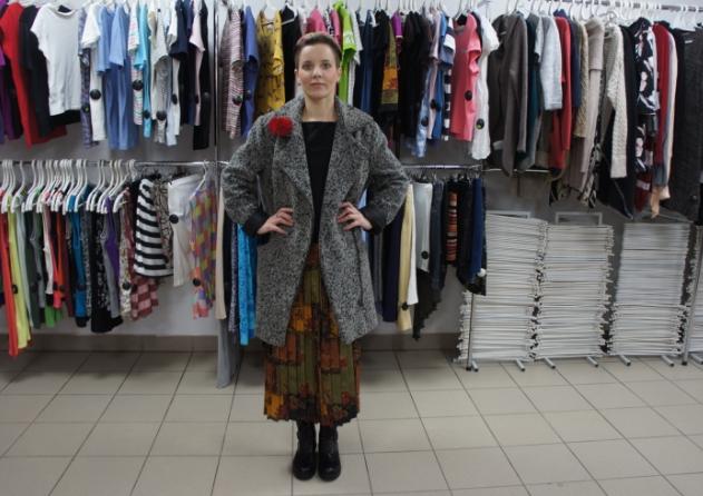 Девушка меряет пальто в магазине одежды