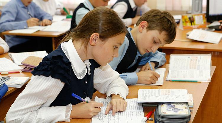 Школьники пишут задание с книги