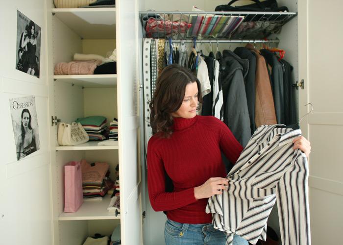 Девушка перебирает вещи в шкафу