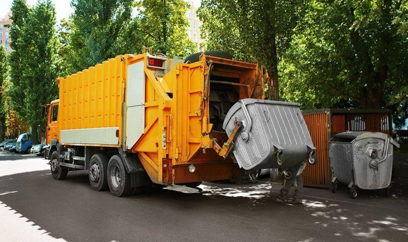 Мусоровоз высыпает мусор из контейнера
