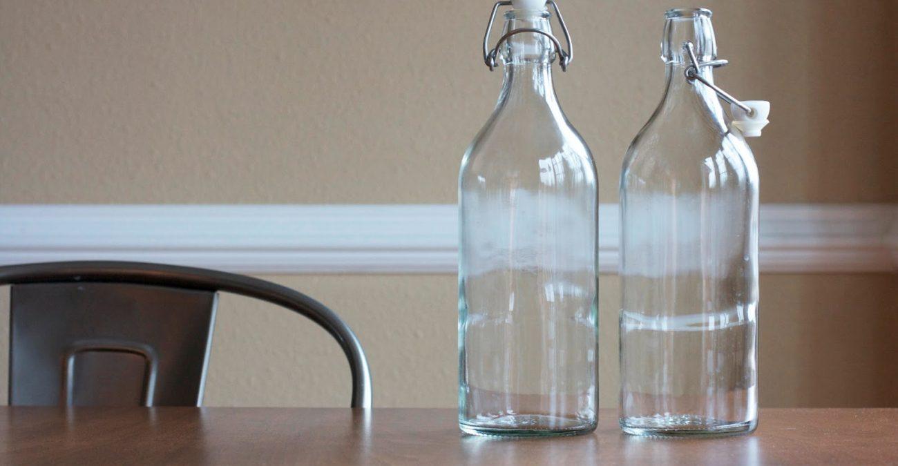 Пустые стеклянные бутылки с откидными пробками на столе