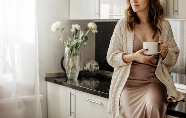 Девушка с чашкой кофе присела на столешницу