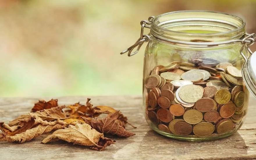 Банка с монетами и опавшими осенними лезвиями