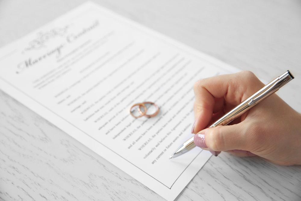 Женская рука с ручкой над листом с кольцами