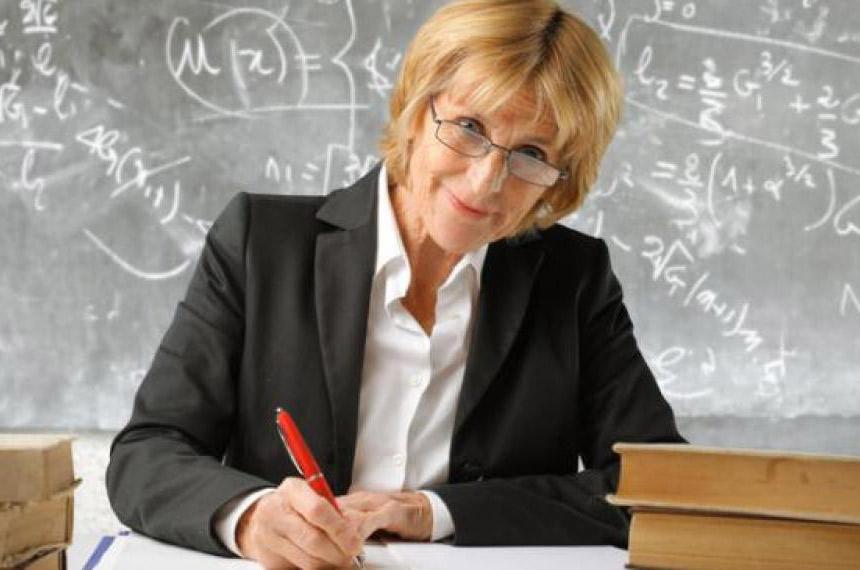 Пожилая учительница улыбается за столом