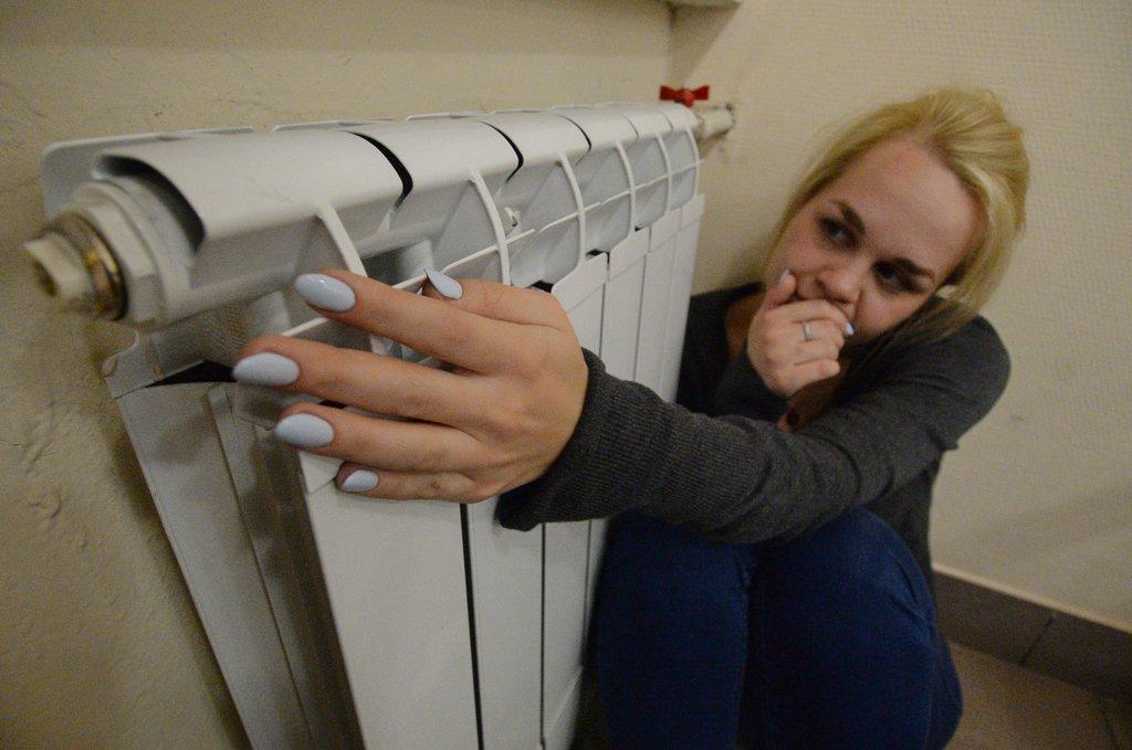 Девушка греется возле радиатора