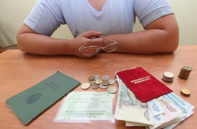 Мужчина и разложенные перед ним документы с деньгами
