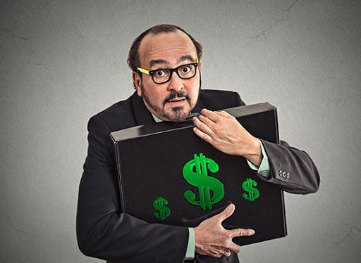 Мужчина в очках прижимает к себе чемодан