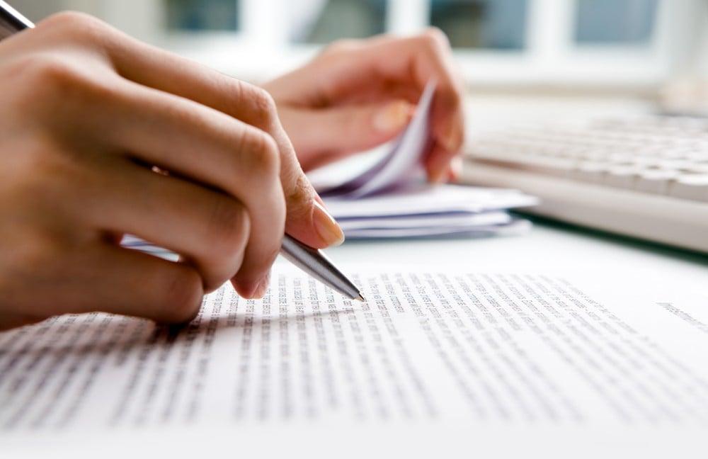 Женская рука подчеркивает ручкой текст