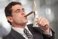 Мужчина прикуриват сигару от долларовой купюры