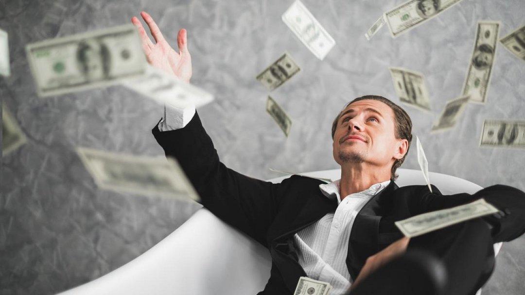 Мужчина бросает доллары, лежа в ванной