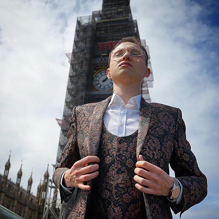 Молодой человек в костюме на фоне британской достопримечательности