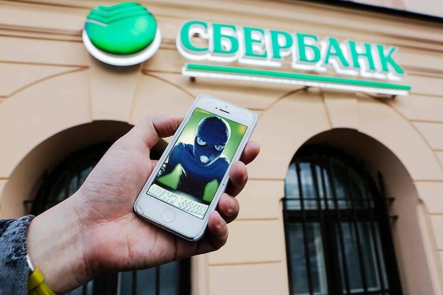 Смартфон в руке на фоне Сбербанка