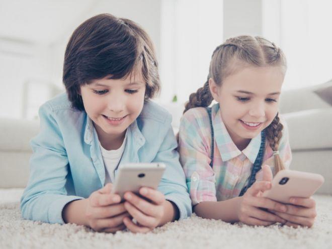 Мальчик и девочка со смартфонами в руках