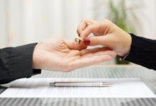 Женщина отдает обручальное кольцо мужчине