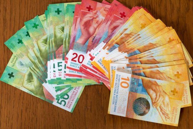 Веер из швейцарских франков на столе