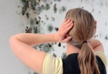 Женщина держится за голову глядя на плесень