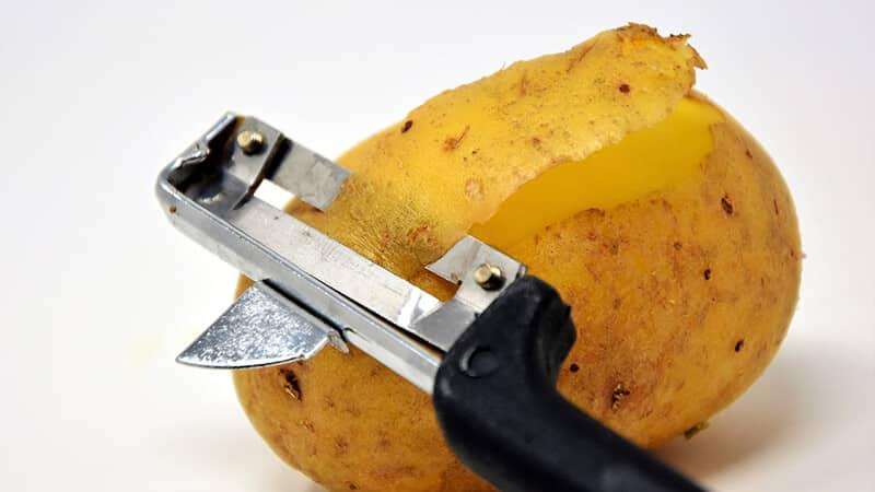 Картофелечистка срезает кожуру с картофеля