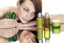 Девушка и косметическое масло во флаконах