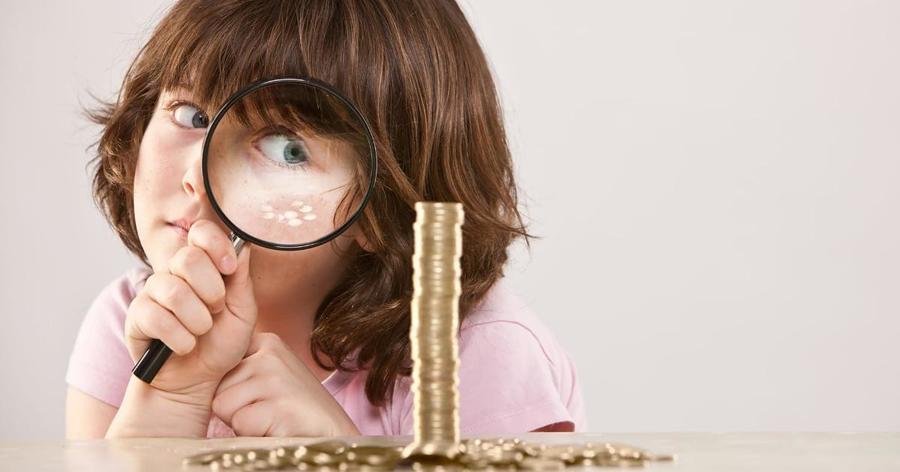 Ребенок смотрит в лупу на монеты
