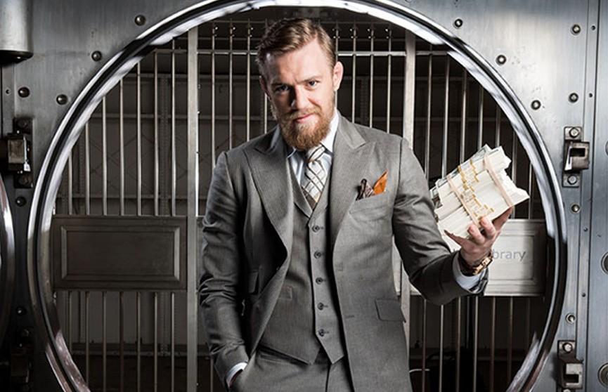 Мужчина в костюме держит пачку денег в руках