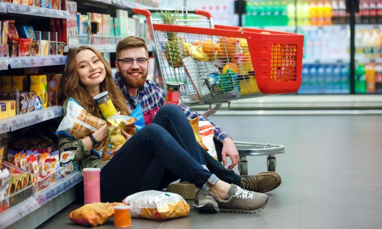 Молодая пара сидит на полу в супермаркете