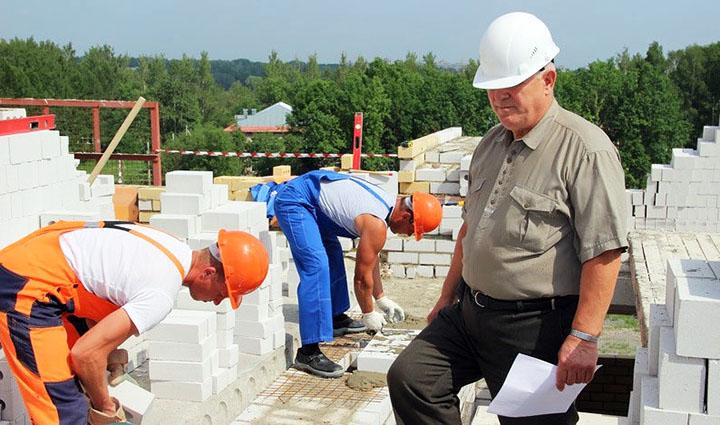 Прораб и рабочие на стройке