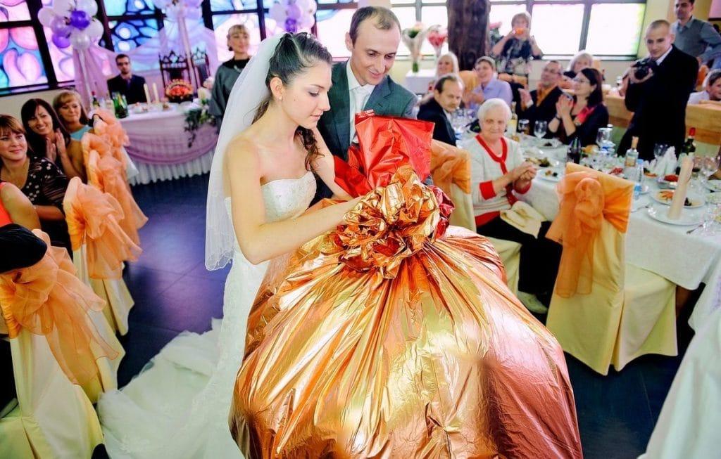 Новобрачные открывают мешок с подарком
