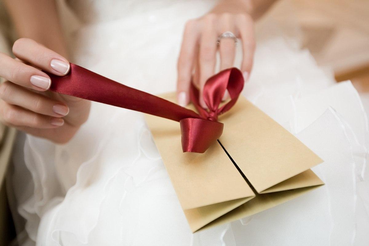 Невеста развязывает ленту на конверте