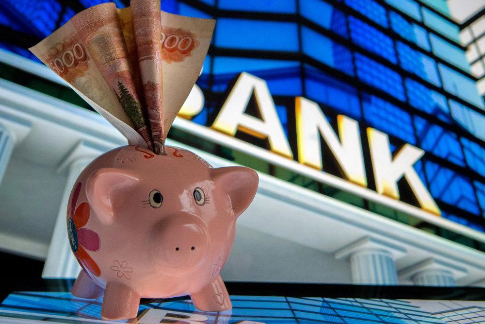 Копилка с торчащей купюрой на фоне банковской вывески