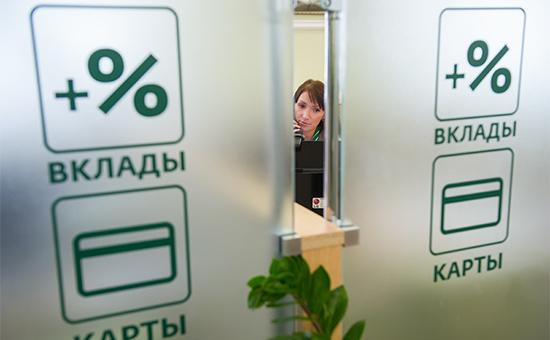 Сотрудник банка говорит по телефону за ширмой с изображенными процентными ставками