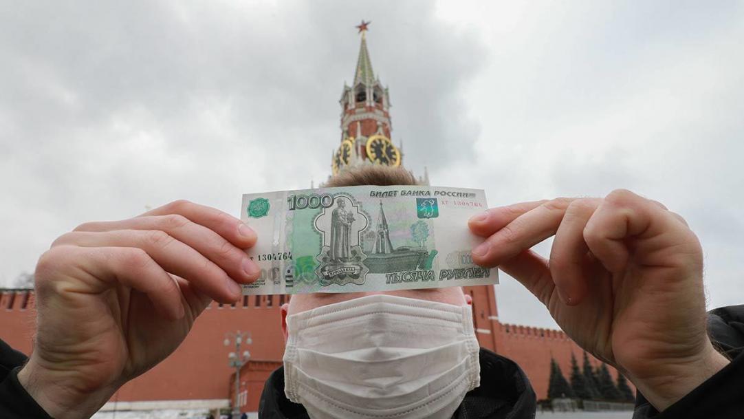 Мужчина в маске на фоне Кремля рассматривает купюру