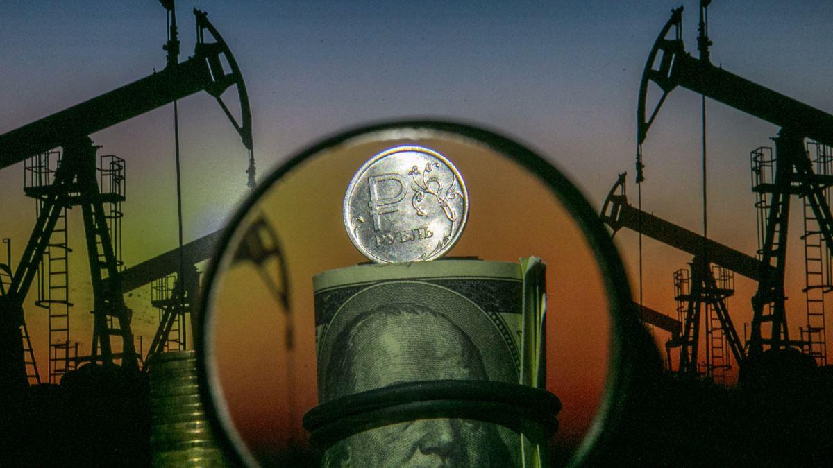 Рубль через увеличительное стекло на фоне нефтяных вышек