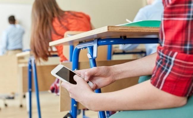 Ученик держит под партой смартфон