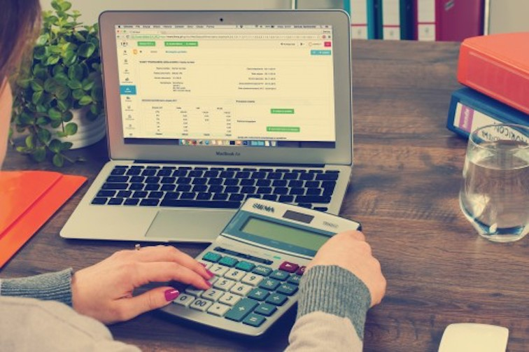 Женщина работает за ПК с калькулятором