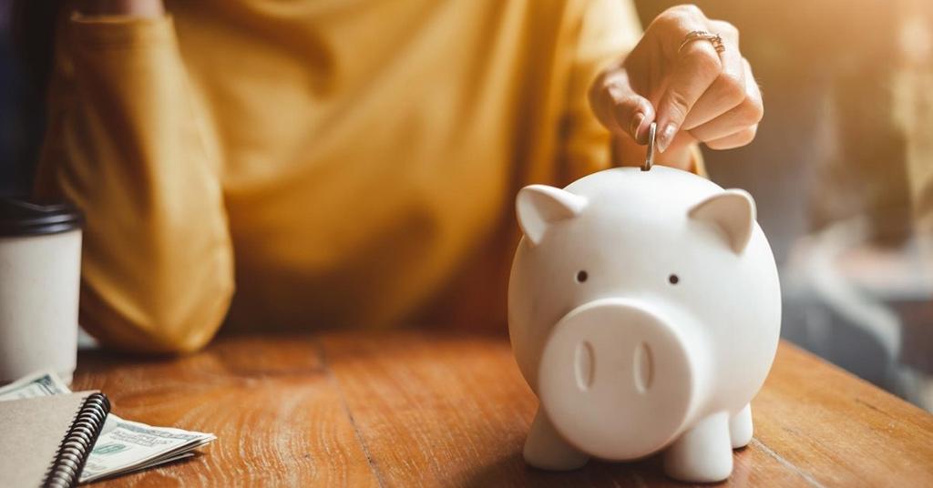 Женщина кладет монетку в копилку-свинью