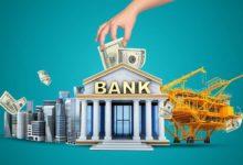Здание банка и рука инвестора с деньгами сверху