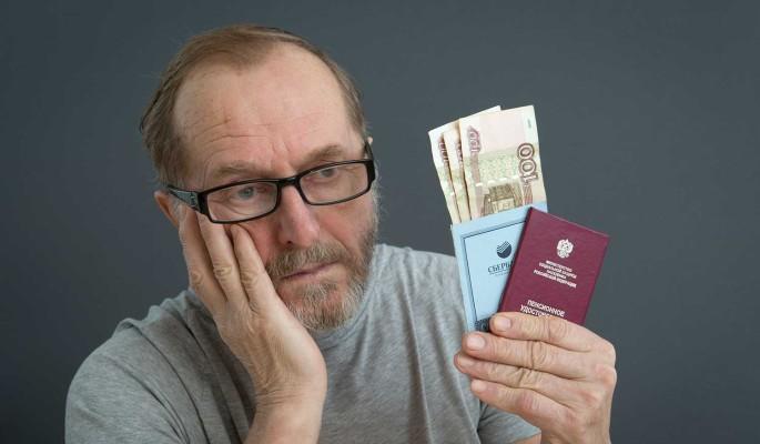 Пожилой мужчина в раздумьях держит документы и деньги в руках