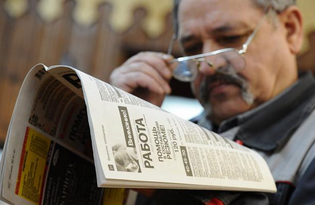 Пожилой мужчина в очках читает газету