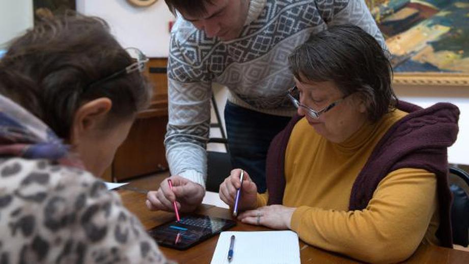 Две женщины и мужчина производят расчеты на калькуляторе