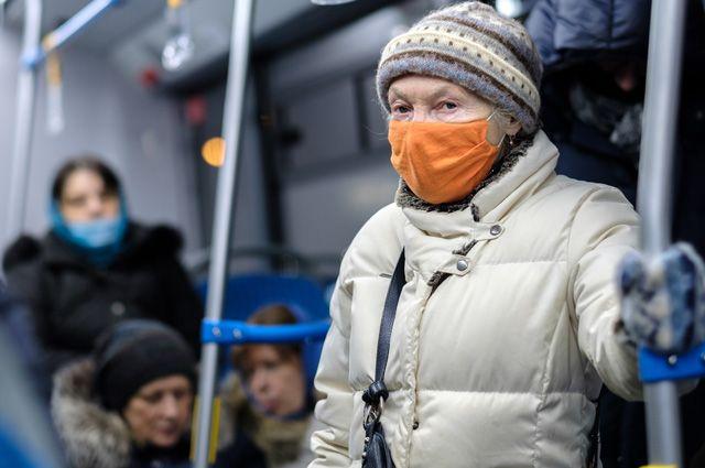 Пожилая женщина в маске едет в метро