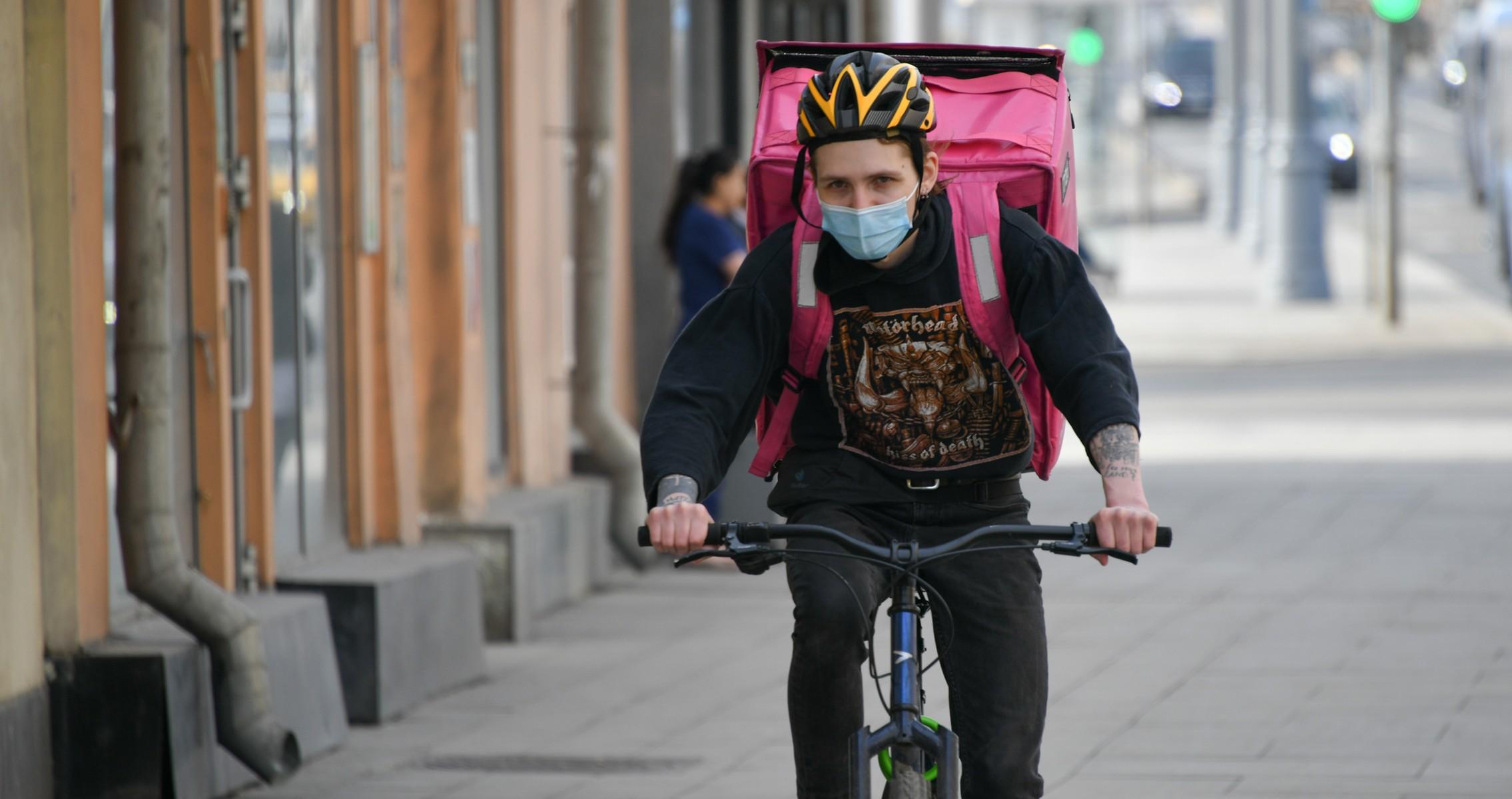 Курьер на велосипеде везет заказ