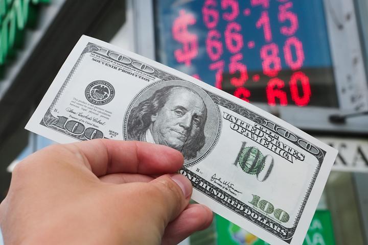 100-долларовая купюра в руке