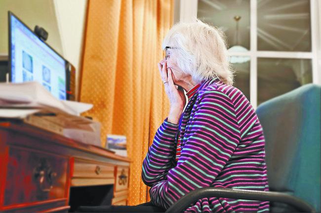 Пожилая женщина сидит за ПК