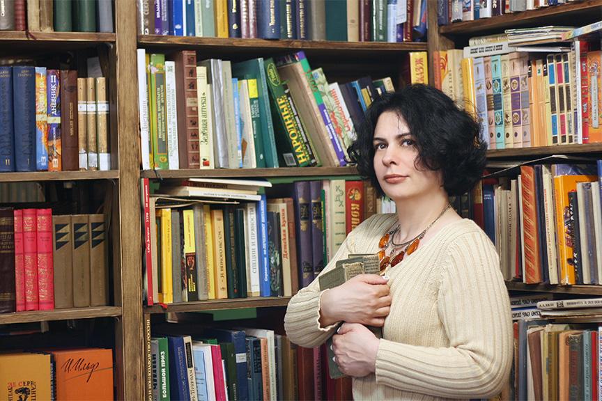 Женщина в библиотеке прижимает к груди книги