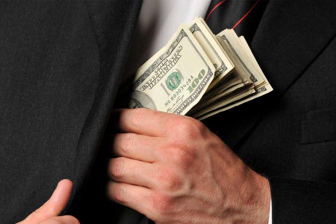 Мужские руки прячут стодолларовые купюры в нагрудный карман своего пиджака